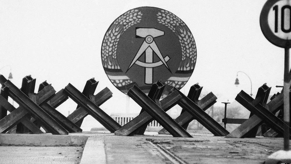 Герб ГДР и противотанковые заграждения. 4 декабря 1961. AP Photo/E.Worth