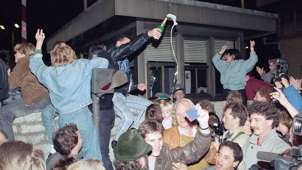 Жители Восточного и Западного Берлина празднуют объединение.10 ноября 1989.  AP Photo/Jockel Finck