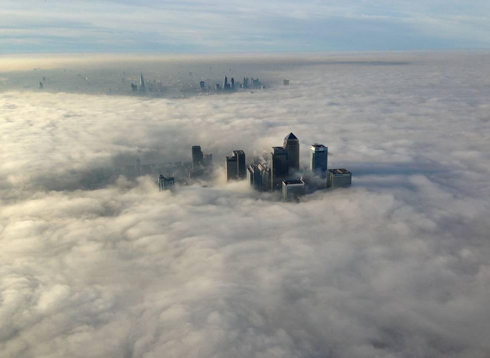 Небоскребы Лондона видны через облака. Кадр сделан из вертолета спецподразделения лондонской полиции Metropolitan police. 12 декабря 2013 года