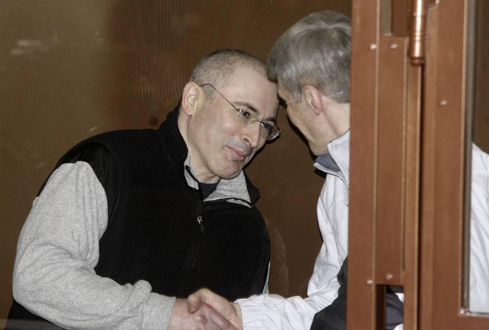 3 марта 2009. Михаил Ходорковский, слева, пожимает руку со своим партнером Платоном Лебедевым за решеткой в зале суда в Москве.