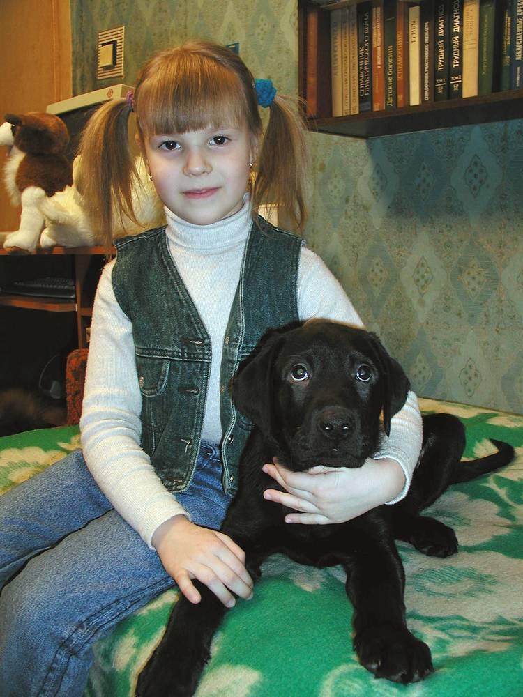 Шестилетняя Катя Сергиенко и щенок лабрадора по кличке Оскар, которого ей подарил Владимир Путин. 26 февраля 2004 г.