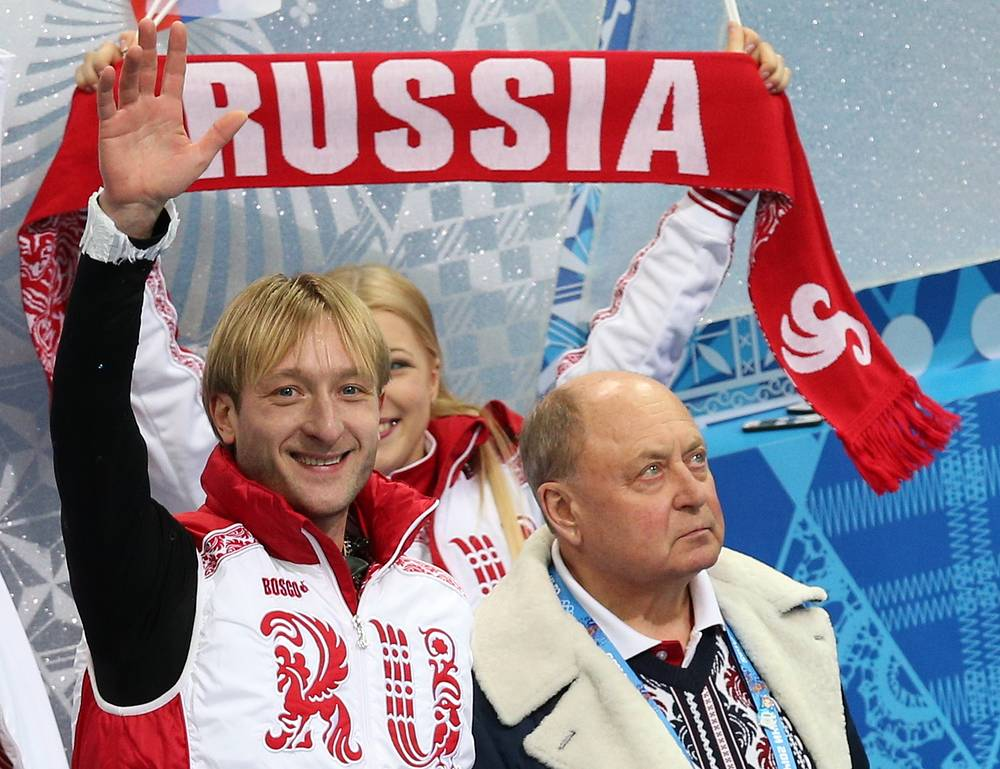 Российский фигурист Евгений Плющенко и его тренер Алексей Мишин (слева направо) во время командных соревнований по фигурному катанию в Сочи