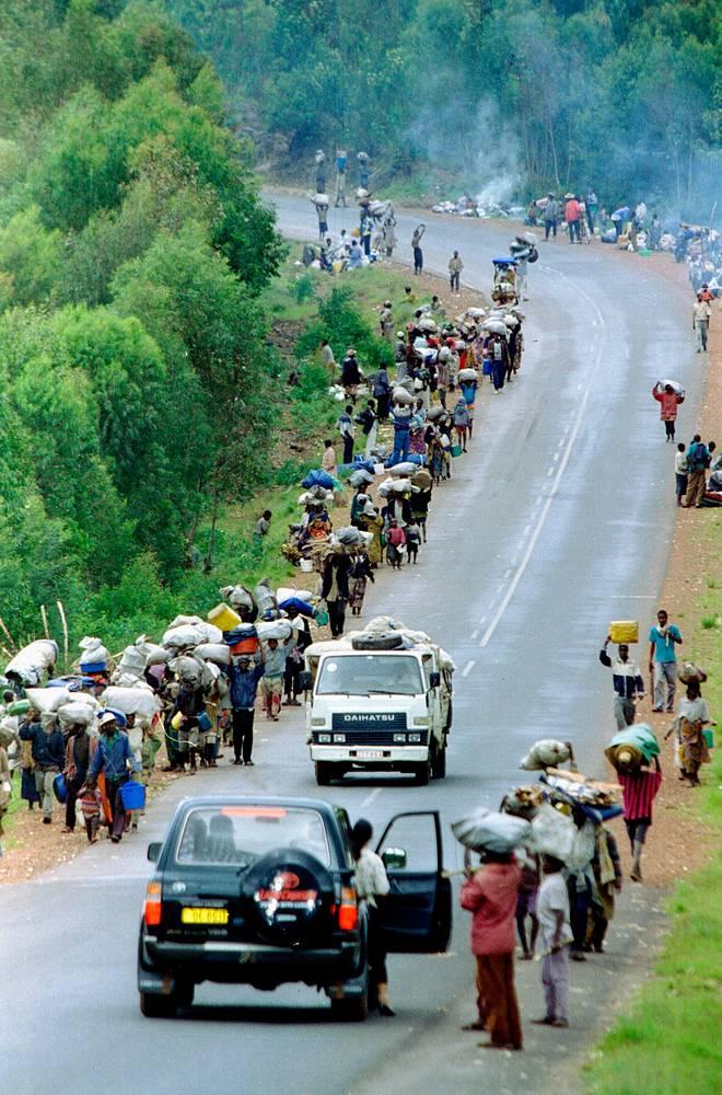 """Радиоведущий Жорж Руджу, призывавший убивать тутси, которых он называл тараканами, получил 12 лет тюрьмы. Редактор газеты """"Кангура"""" Хассан Нгезе по решению суда проведет в тюрьме оставшиеся годы. На фото: поток беженцев движется от границы Заира в сторону Кигали, 1996 год"""