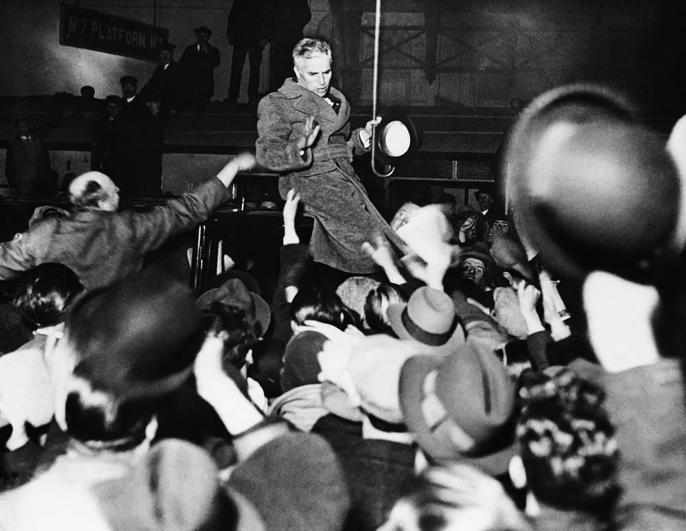 Чаплин приветствует своих поклонников на железнодорожной станции в Лондоне, 1931 год