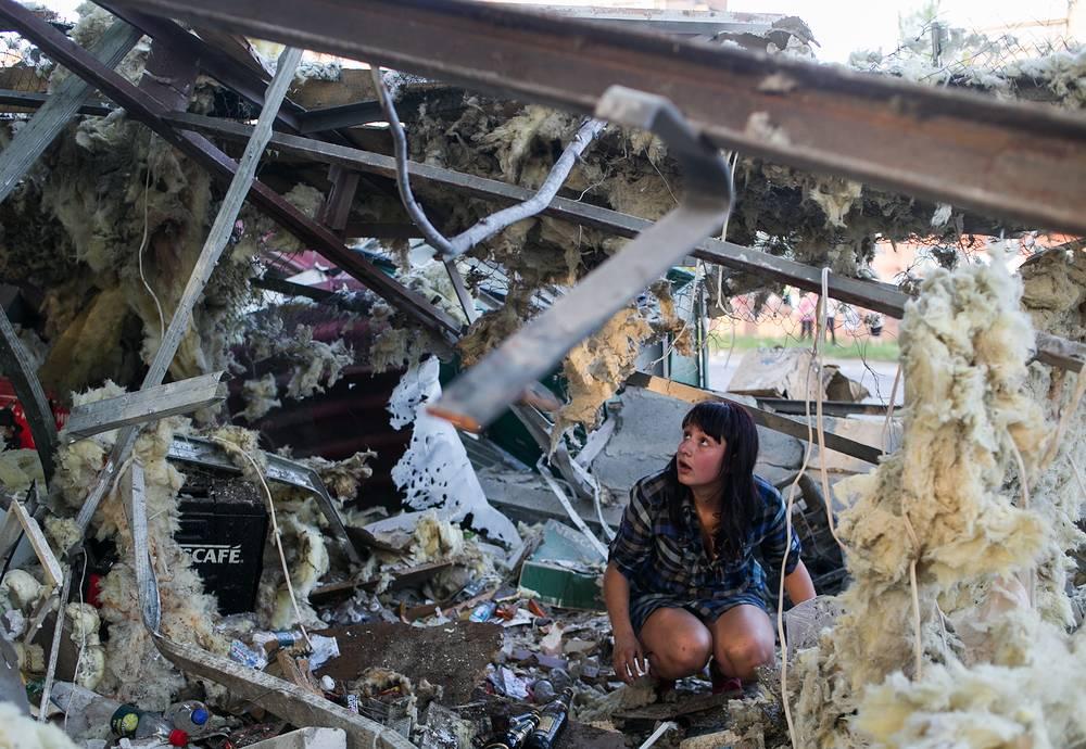 Обстрелу подверглись жилые кварталы, предприятия города, в том числе очистные сооружения. На фото: жительница Краматорска у разрушенного продуктового магазина