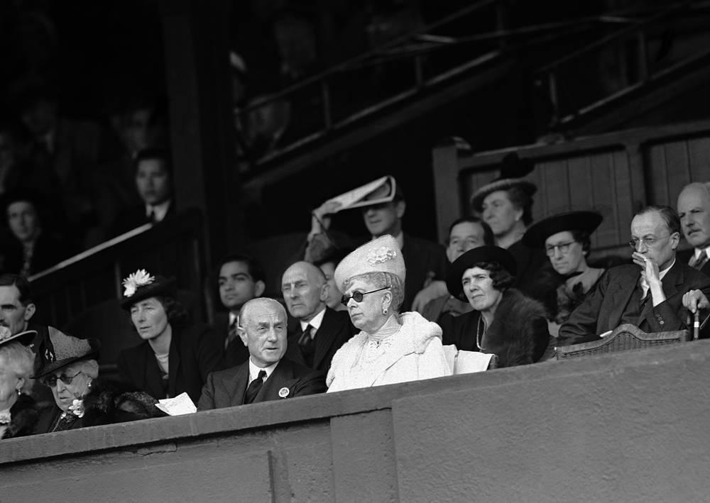 Королева Великобритании Мэри, в темных очках, и сэр Сэмюэль Хор, министр внутренних дел, который также являлся президентом Британской ассоциации лаун-тенниса, наблюдают теннисный матч из королевской ложи на центральном корте Уимблдона. 26 июня 1939 года
