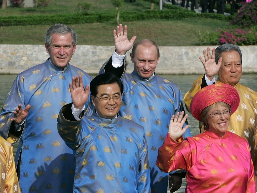 Президенты США Джордж Буш, России Владимир Путин и премьер-министр Таиланда Сураюд Чуланот (во втором ряду), председатель КНР Ху Цзиньтао и президент Чили Мишель Бачелет во вьетнамских национальных костюмах в ходе встречи лидеров АТЭС, Вьетнам, 2006 год