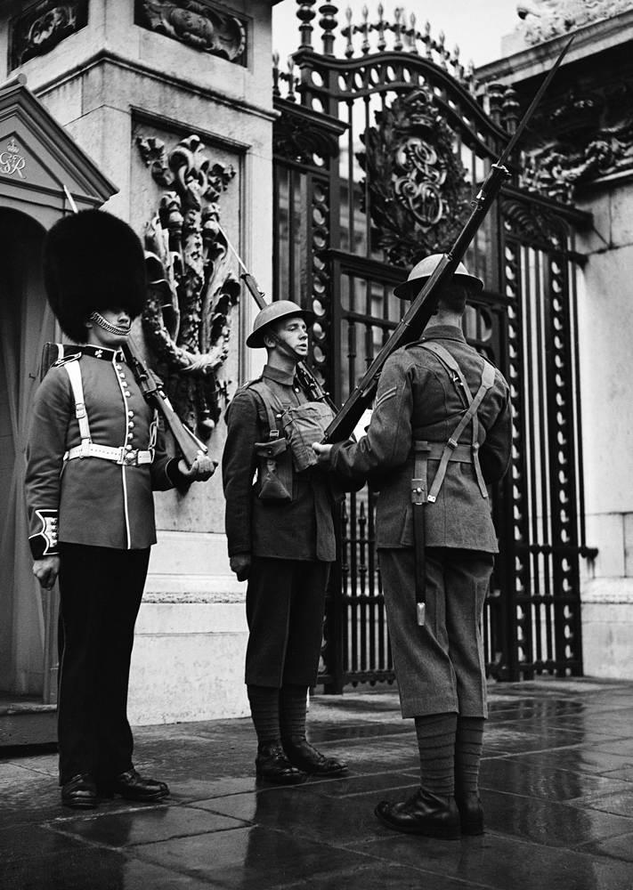 Гвардейцы в военной форме, оснащенные противогазами, приходят на смену гвардейцу в традиционной форме у Букингемского дворца в Лондоне. 1 сентября 1939 года
