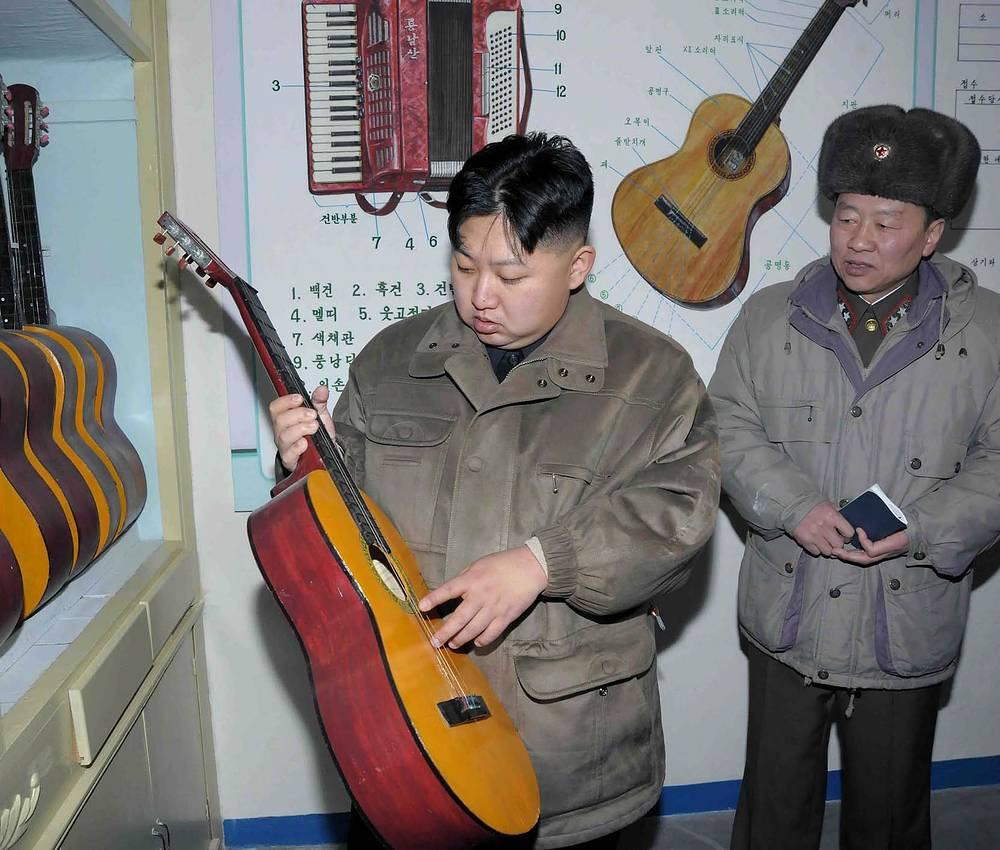 Ким Чен Ын рассматривает гитары во время визита в военную часть, 2011 год