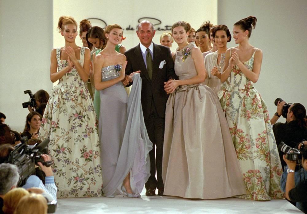 Дизайнер Оскар де ла Рента позирует с моделями во время показа весенней коллекции одежды в Нью-Йорке, 1995 год