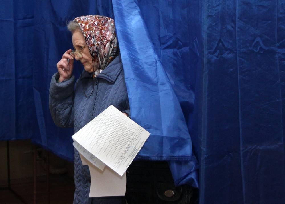 Голосование завершилось в 20:00 (21:00 мск). На фото: Женщина во время голосования на досрочных выборах в Киеве