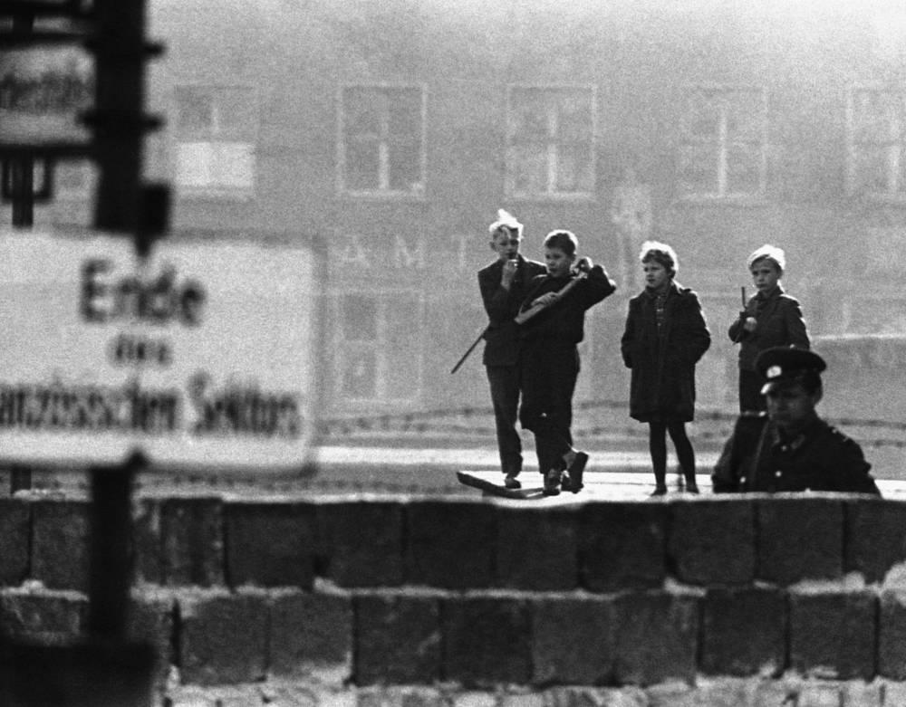 Действовало 8 внутригородских КПП и 6 - между ГДР и Западным Берлином, а также несколько КПП для транзитного транспорта. На фото: дети из Восточного Берлина играют с игрушечными ружьями возле границы с Западным Берлином на улице Бернауэрштрассе, 1962 год