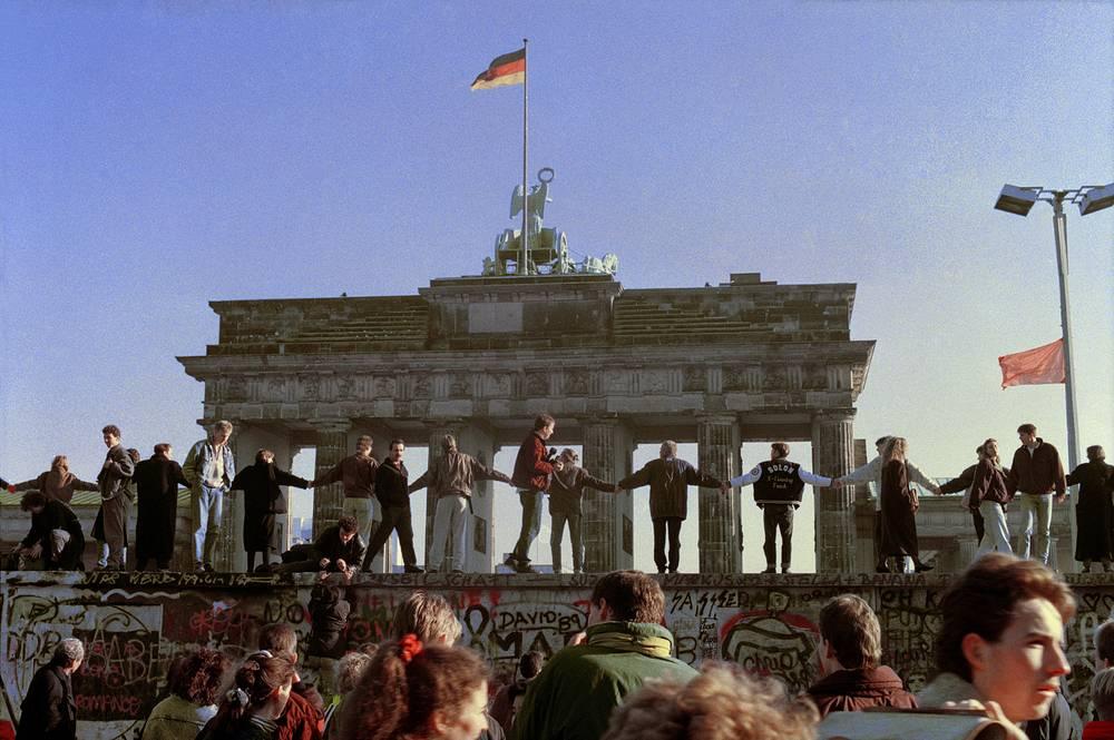 3 октября 1990 года Западный Берлин прекратил свое существование, столицей страны стал Берлин. На фото: берлинцы празднуют открытие границ между восточной и западной частями города, 1989 год