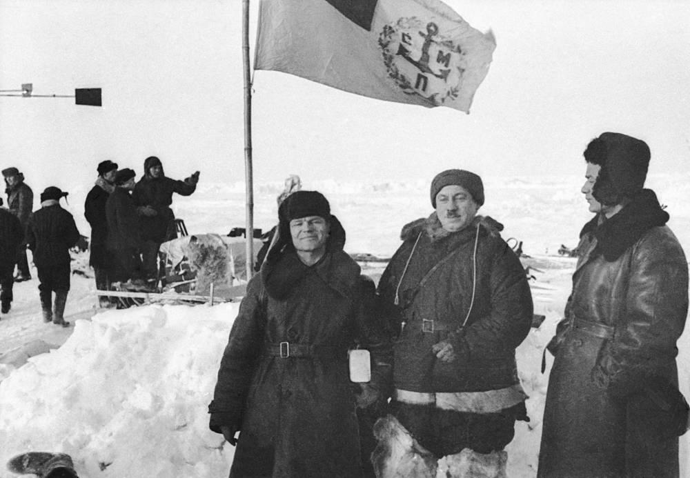 """С конца января 1938 года льдина непрерывно уменьшалась. Вскоре полярникам пришлось послать радиограмму, в которой говорилось, что экспедиция находится на обломке длиной 300 м, шириной 200 м и что наметилась трещина под жилой палаткой. На спасение полярников были направлены пароход """"Мурманец"""", а затем и ледоколы """"Мурман"""" с """"Таймыром"""". Последние два сняли папанинцев с льдины. На фото: летчик Геннадий Власов, Папанин и начальник экспедиции по спасению папанинцев на ледоколе """"Таймыр"""" Ананий Остальцев"""