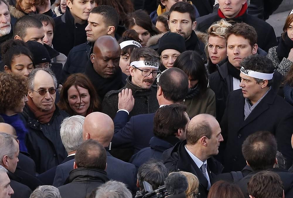 Президент Франции Франсуа Олланд общается с сотрудниками редакции Charlie Hebdo карикатуристом Ренальдом Лузье (в центре) и редактором Патриком Пеллу (справа) и родственниками погибших журналистов издания Charlie Hebdo