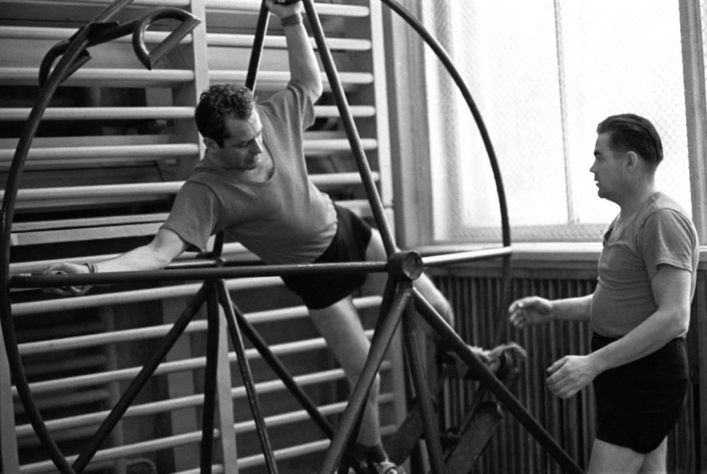 """Герман Титов и Андриян Николаев (слева направо) во время тренировки, 1964 год. Титов был вторым космонавтом СССР и Земли. Был первым дублером Юрия Гагарина перед полетом корабля """"Восток"""" (1961). Совершил один космический полет. 6-7 августа 1961 г. пилотировал корабль """"Восток-2"""", впервые полет в космос длился более суток. Отчислен из отряда космонавтов 17 июня 1970 г.  Николаев служил в авиации сил противовоздушной обороны. Совершил два космических полета. Первый 11-15 августа 1962 г. на корабле """"Восток-3"""". Второй - 1-19 июня 1970 г. в качестве командира корабля """"Союз-9"""". Отчислен из отряда 26 января 1982 г."""