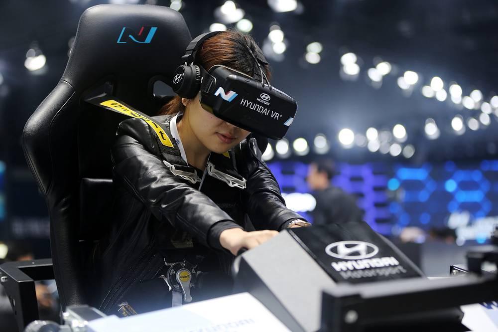 Посетительница автосалона испытывает симулятор виртуальой реальности Hyundai