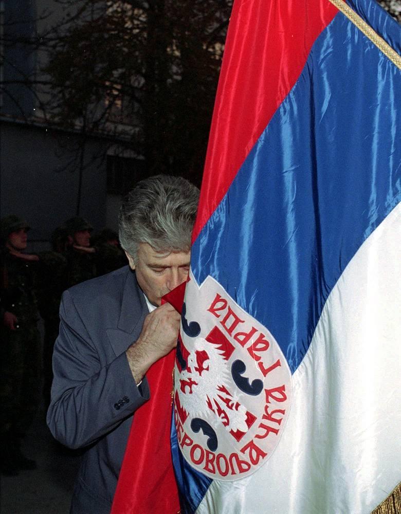 Караджич целует военный флаг Сербской добровольческой гвардии Желько Ражнатовича (Аркана) 23 октября 1995 года в Биелине, около 140 км (95 миль) к западу от Белграда