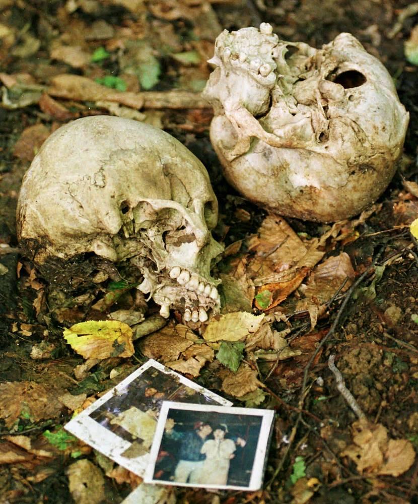 Семейные фотографии и черепа, найденные экспертной комиссией по военнопленным и без вести пропавшим лицам у деревни Кравице, к северу от Сребреницы, 17 сентября 1996 года