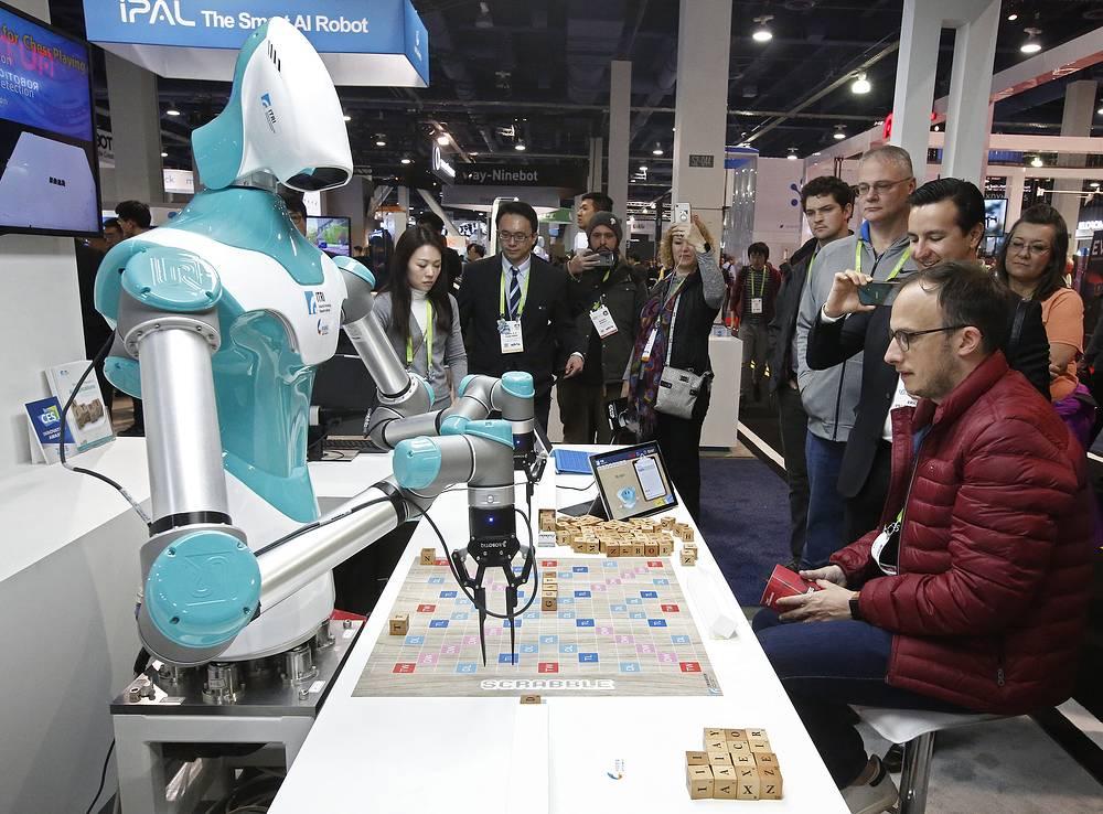 Посетитель выставки играет с роботом