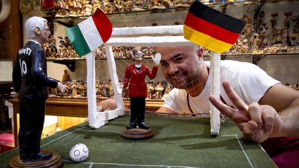 Художник из Неаполя и его интерпретация матча с куклами, изображающими Марио Монти и Ангелу Меркель