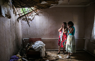 Residents of Ukraine's Sloviansk in their destroyed house