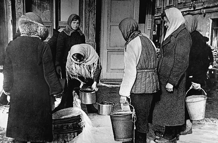 Ленинградцы берут воду у действующего водопроводного крана в одном из дворов на Невском проспекте. Март 1942 года.