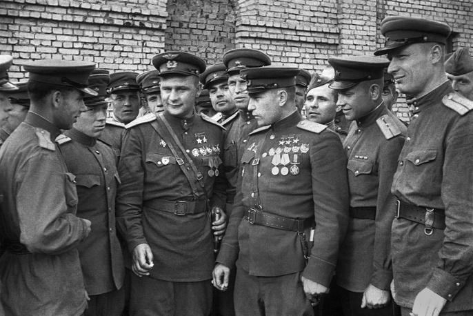 Трижды Герой Советского Союза Александр Покрышкин и дважды Герой Советского Союза Дмитрий Глинка (в центре справа налево) беседуют с участниками парада Победы, 1945