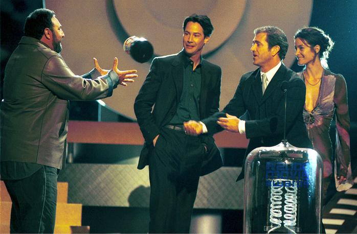 """Фильм получил более 30 кинопремий. На фото: ведущий церемонии MTV Movie Awards Мэл Гибсон (второй справа) бросает награду """"Самый лучший фильм"""" продюсеру фильма """"Матрица"""" Джоэлу Силверу (слева), на заднем плане Киану Ривз и Кэрри Энн Мосс, 2000 год"""