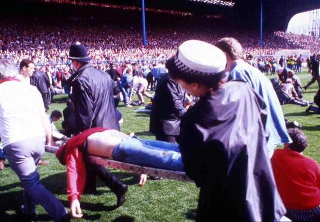 В связи с плохой пропускной способностью турникетов командующий безопасностью на стадионе шеф полиции Дэвид Дакенфилд спросил у толпы о наличии билетов на матч, после чего приказал подчиненным пускать всех собравшихся без контроля билетов. На фото: полиция и стюарды помогают пострадавшим в результате давки на стадионе, 15 апреля 1989 года