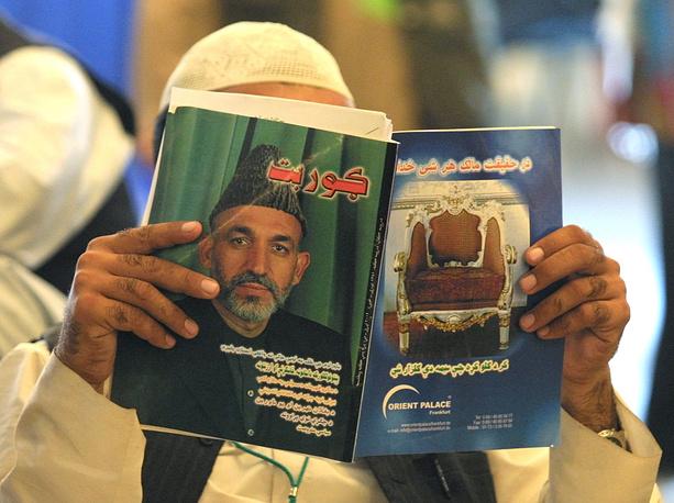 Несмотря на давление со стороны Вашингтона, Хамид Карзай отказался подписать соглашение об американской военной помощи с конца 2014 года. На фото: делегат всеафганского совета старейшин читает журнал с портретом Карзая на обложке