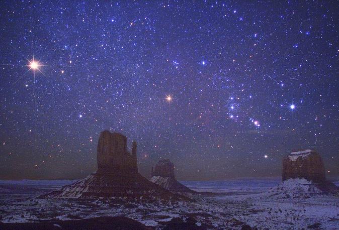 Марс и Орион над долиной Монументов в США. Слева на небе видна Красная планета, справа от нее - созвездие Орион, в центре - звезда Бетельгейзе, еще правее расположены пояс и туманность Ориона, а также яркая голубая звезда Ригель