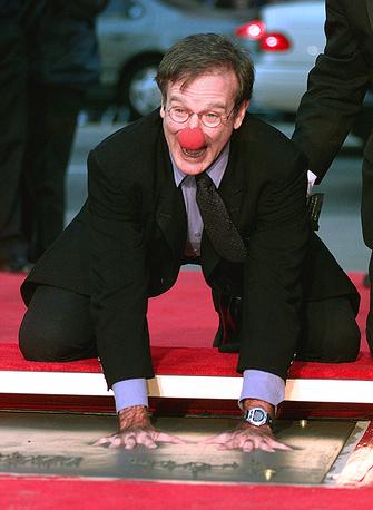 """Робин Уильямс с красным носом из фильма """"Целитель Адамс"""" опускает руки в цемент, чтобы оставить свои отпечатки, Лос-Анджелес, 1998 год"""