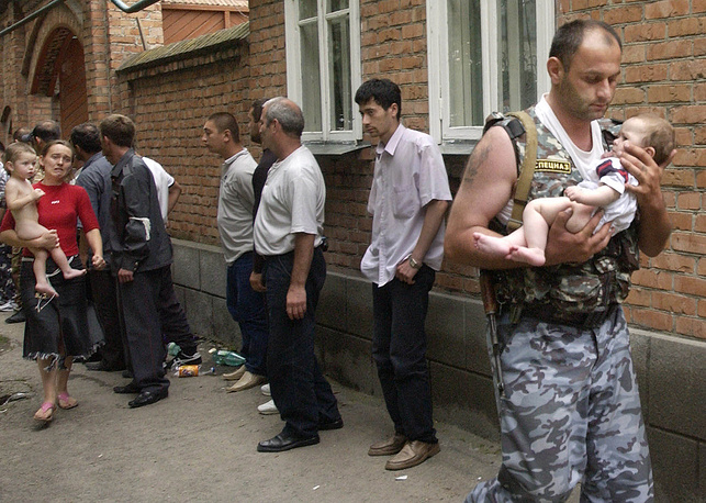 Спецназовец (справа) выносит освобожденного боевиками шестимесячного ребенка из здания школы, 2 сентября 2004 года