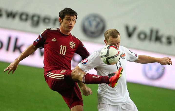 Игроки сборных России Алан Дзагоев и Лихтенштейна Мартин Бюхель (слева направо)