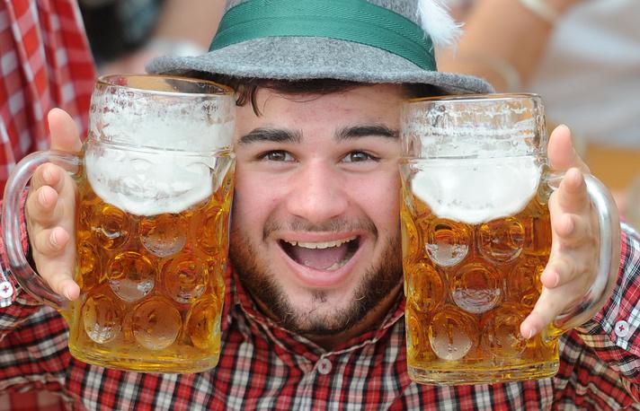 Посетитель позирует с двумя пивными кружками на фестивале в Мюнхене