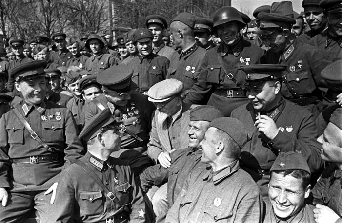 """Следующий закон """"О всеобщей воинской обязанности"""", регламентирующий формирование советской армии, был принят в 1939 году. По нему граждане СССР без различия расы, национальности, вероисповедания, образовательного ценза, социального происхождения и положения обязаны были отбывать военную службу. На фото: Михаил Калинин среди награжденных бойцов Красной Армии, 1940 год"""
