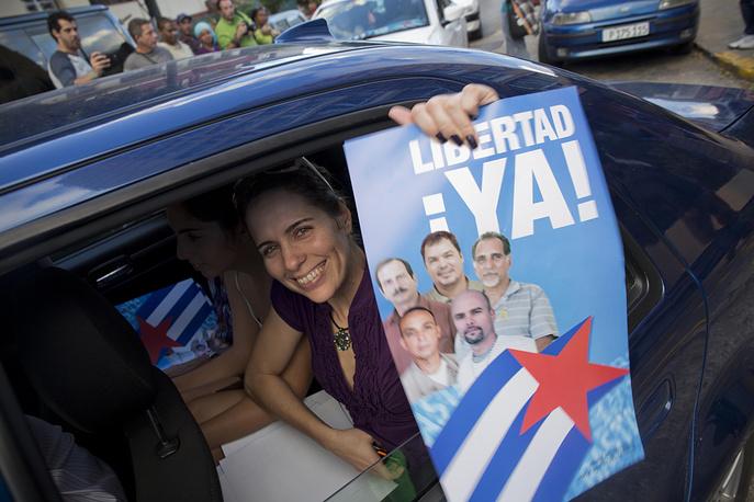 США в свою очередь освободили троих кубинских разведчиков, отбывавших наказание в американских тюрьмах. Речь идет о кубинских агентах из так называемой героической пятерки, двое из которых были освобождены ранее. На Кубе их называют национальными героями. На фото: жительница Гаваны держит плакат в поддержку героической пятерки