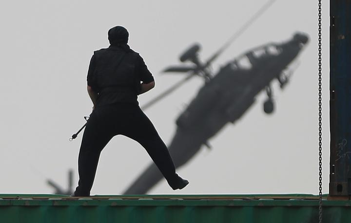 Боец спецназа вооруженных сил ОАЭ в ходе показательного выступления на выставке IDEX 2015. На заднем плане - ударный вертолет McDonnell Douglas AH-64 Apache Longbow
