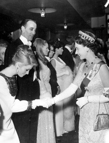 Королева Великобритании Елизавета II приветствует актеров Катрин Денев и Кристофера Ли перед королевским киносмотром в театре Одеон в Лондоне. 1966 год