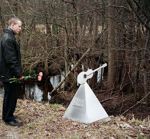 """На 35-м километре трассы Слока - Талси в Латвии установлено сразу несколько памятников Цою. На фото: поклонник на месте гибели лидера группы """"Кино"""", 2002 год"""