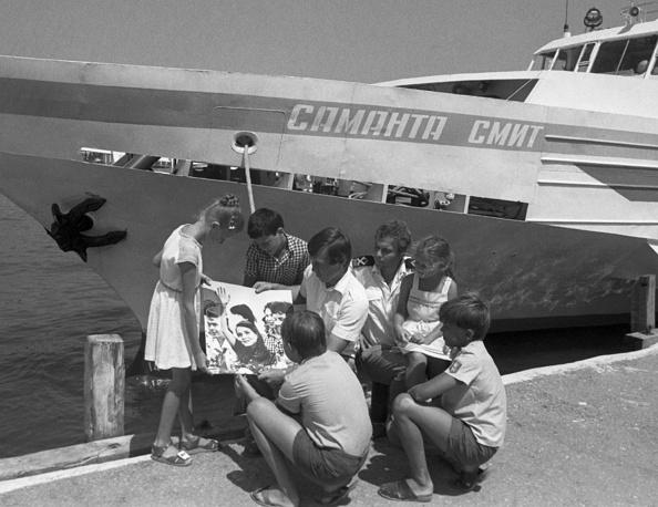 """Прогулочный теплоход """"Саманта Смит"""" у причала. Члены экипажа показывают детям фотографии Саманты Смит. Ялта, 24 июня 1986 года"""
