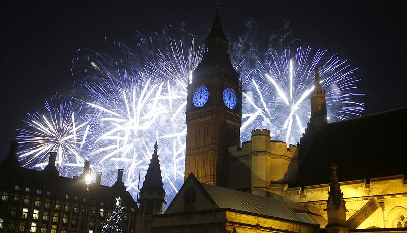 Лондон. Великобритания. 1 января 2016. Салют над рекой Темзой и Вестминстерским дворцом, известным также как Биг Бен.