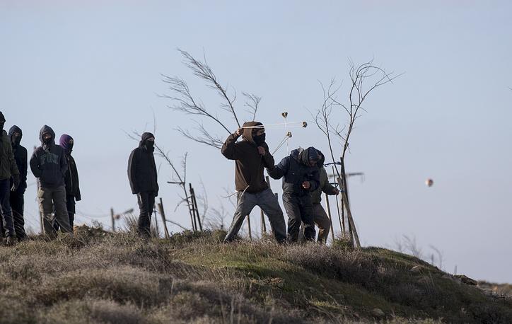 Поселенцы бросают камни в полицейских