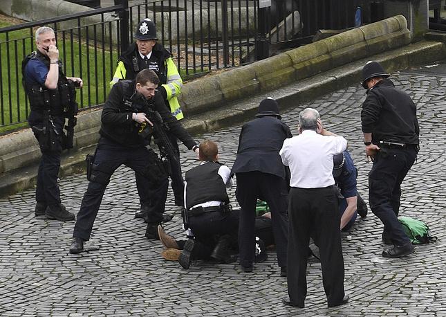 Полицейский держит на прицеле одного из нападавших, Лондон, 22 марта