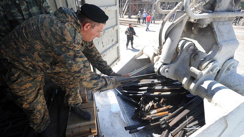 Сотрудник правоохранительных органов выгружает изъятое оружие