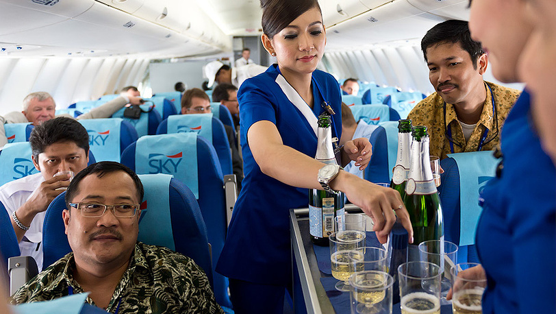 """Пассажиры и стюардессы в салоне авиалайнера Superjet-100 в аэропорту """"Халим Перданакусума"""" перед показательным полетом"""