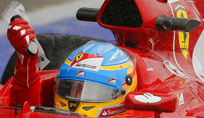 Шлем гонщика «Формулы-1» команды «Феррари» Фернандо Алонсо с оранжевой звездой - логотипом де Вильоты- в поддержку гонщицы, попавшей в аварию во время заездов. Фото EPA/ GEOFF CADDICK