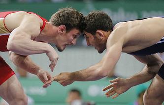 Российский спортсмен Александр Богомоев и Гаджи Алиев из Азербайджана (слева направо) в полуфинальных соревнованиях по вольной борьбе в весовой категории до 61 кг