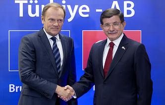 Глава Евросовета Дональд Туск обменивается рукопожатием с турецким премьер-министром Ахметом Давутоглу